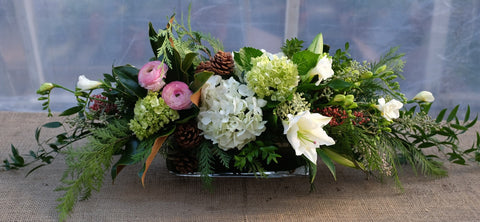 Floral centerpiece with lilies, freesia, ranunculus in a glass rectangular vase | Michler's Florist