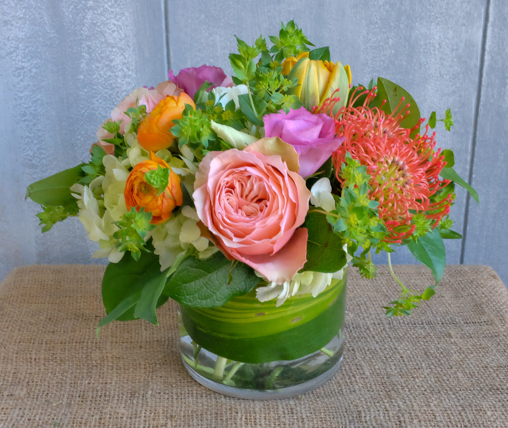 Low and lush centerpiece with Ranunculus, Double Orange Princess Tulips, and Protea | Michler's Florist