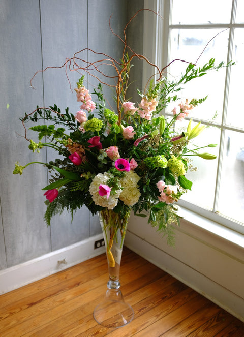 Amsterdam: Tall Martini Glass Floral Arrangement with Anemones,  Roses, Snapdragons and Willow. Designed by Michler's Florist in Lexington, KY
