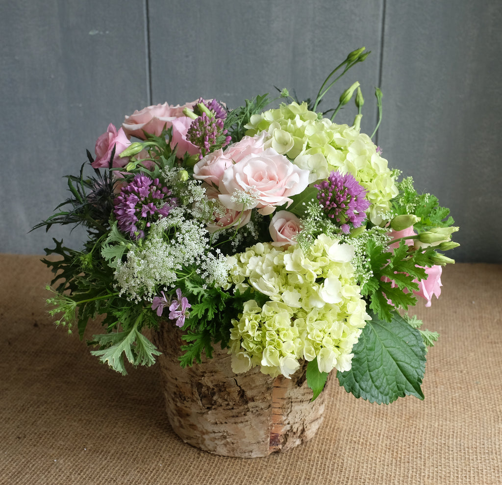 Flower bouquet with pink and green flowers in a birch bark vase