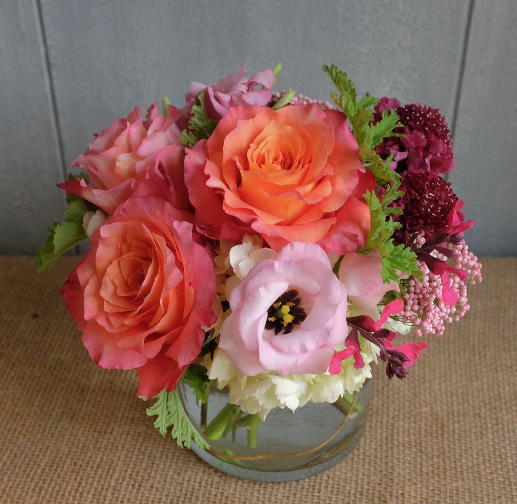 Lush bouquet of flowers in orange pink and raspberry.