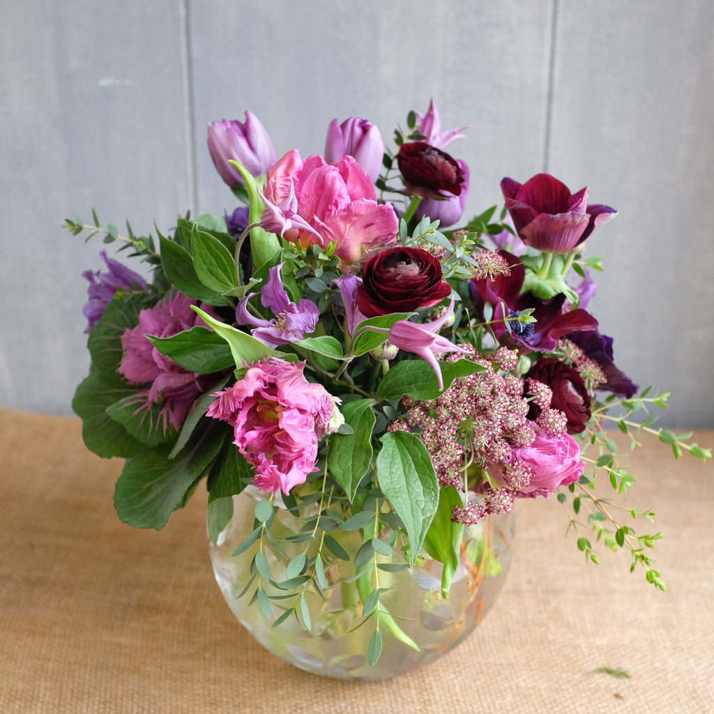 Bubble bowl arrangement with purple flowers by Michler's Florist