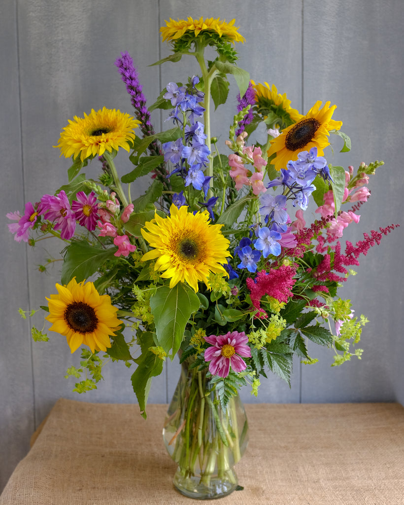 Tall and elegant summer bouquet featuring sunflowers, delphimium, and snapdragons designed by Michlers Florist in clear glass vase