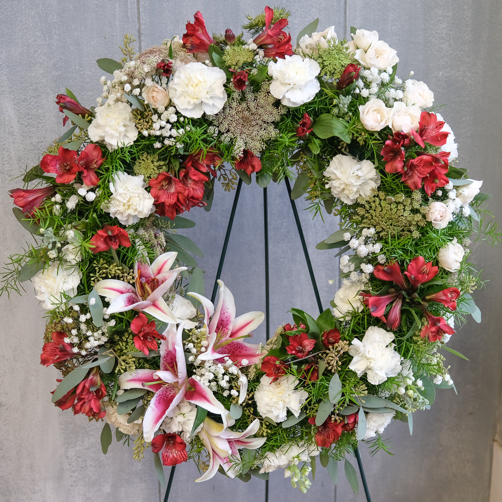 floral sympathy wreath with stargazer lilies, carnations, roses, Queen Anne's lace, and baby's breath by Michler's Florist in Lexington, KY