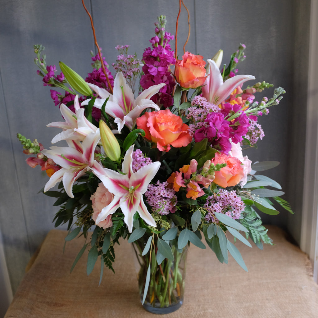 Large bouquet brimming with warm and vibrant flowers.