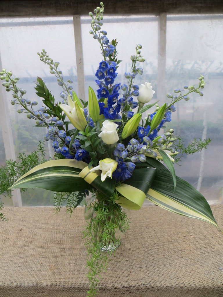Blue and White Flower Arrangement: White Roses, Blue Delphium designed in a glass vase by Michler's Florist in Lexington, KY
