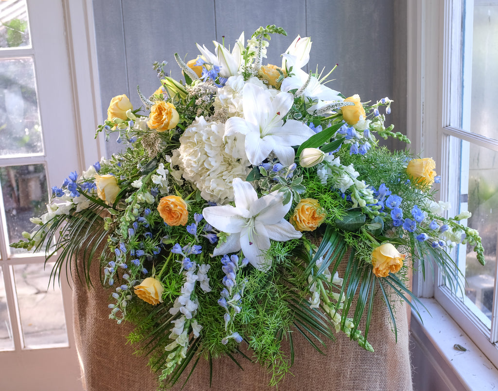 floral casket spray with roses, hydrangea, lilies, and stock by Michler's
