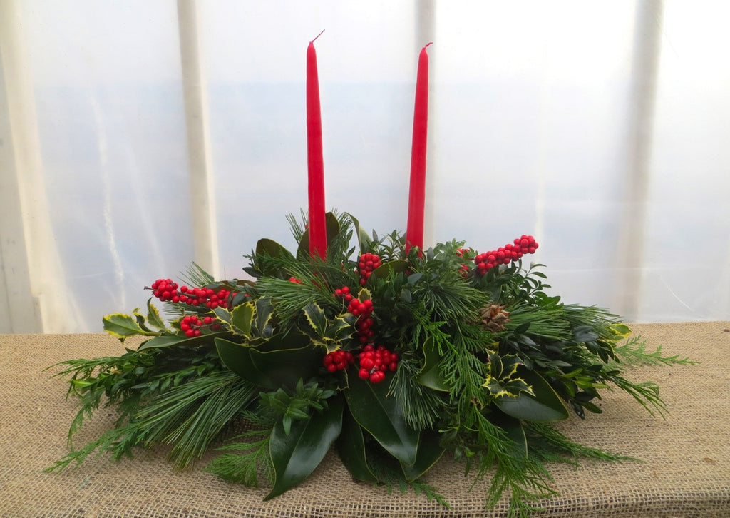 Christmas Centerpiece with Red Candles, Magnolia, and Holly Berries | Michler's Florist