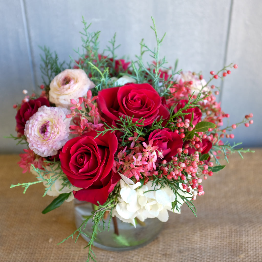 Flower arrangement with pepperberry and cappuccino ranunculus.