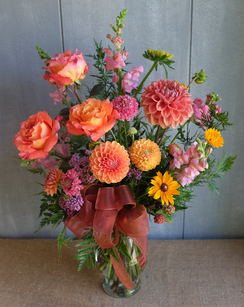 Floral arrangement with peach dahlias, peach roses, black-eyed susan, sunflower by Michler's florist