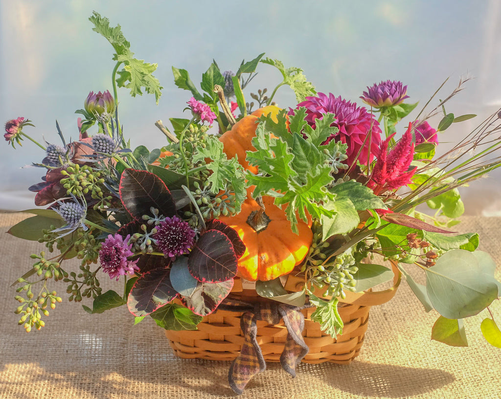 Fun fall basket with pumpkins and seasonal flowers by Michler's Florist.