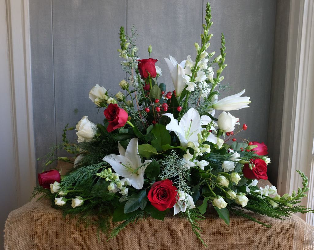 Red and White Christmas flowers with evergreens.  Large all around design by Michler's Florist with roses, snapdragons, berries, and cedar