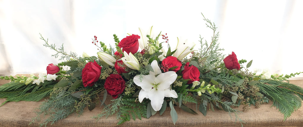Low and long Christmas arrangement with white oriental lilies, red roses, and evregreens
