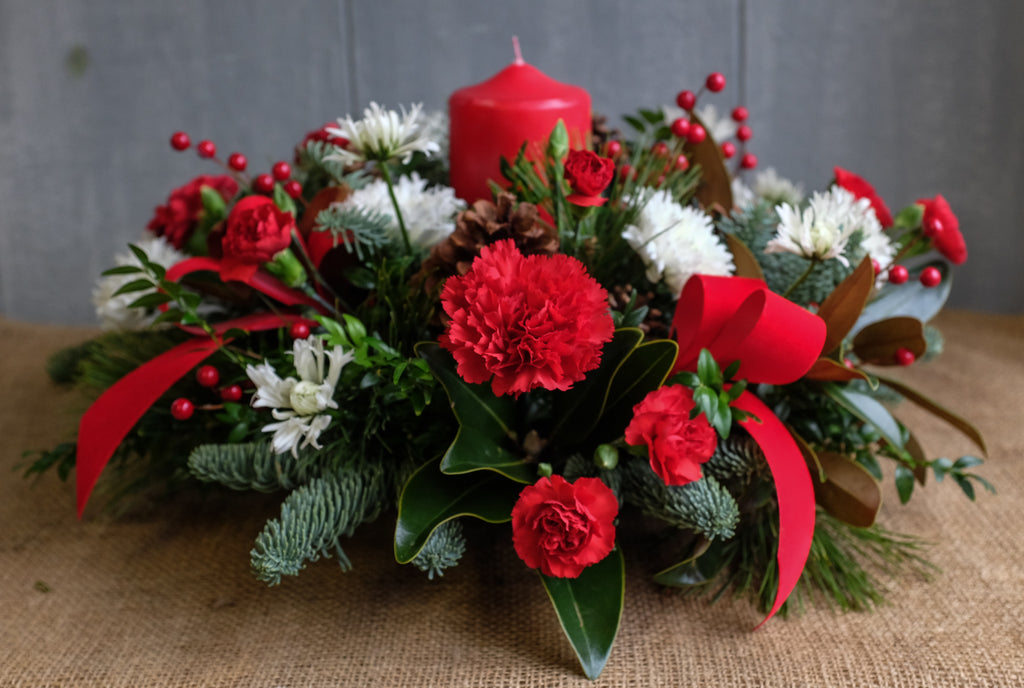 Floral centerpiece with carnations, mums, red bows, magnolia leaves, pine cones, and red pillar candle by Michler's Florist
