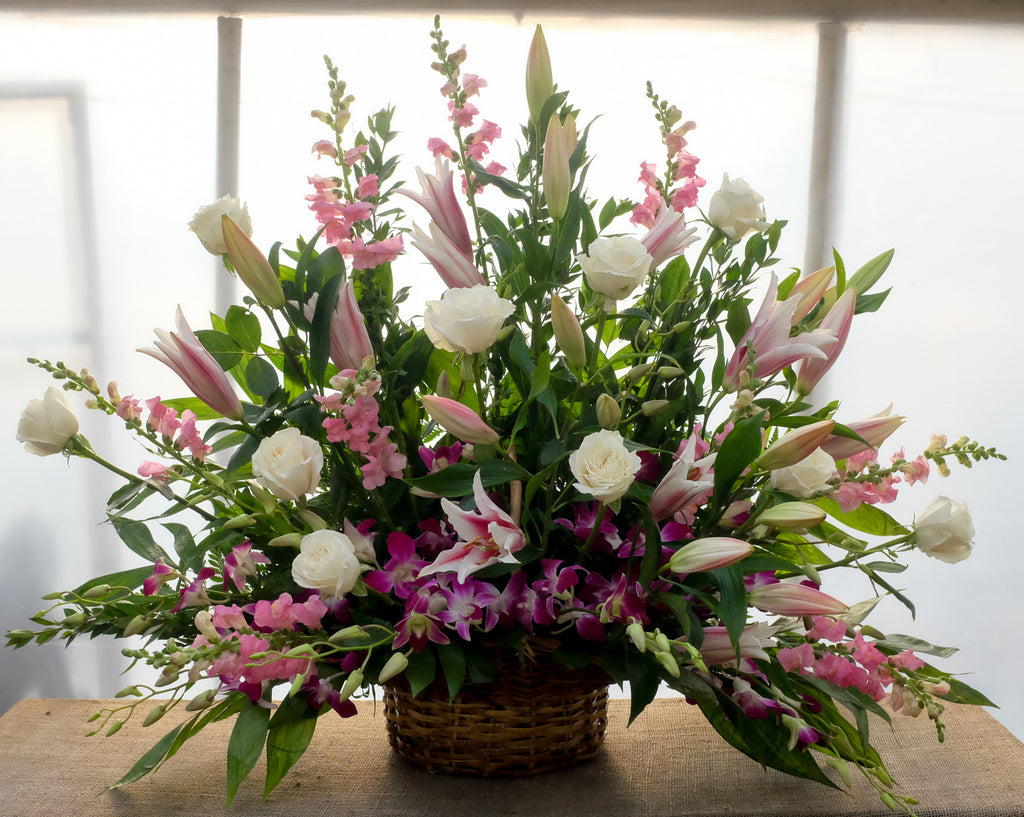 A funeral floral basket with stargazer lilies, pink snapdragon, white roses, dendrobium