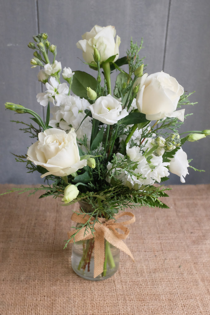 Simple clear glass vase of seasonal white flowers and evergreens