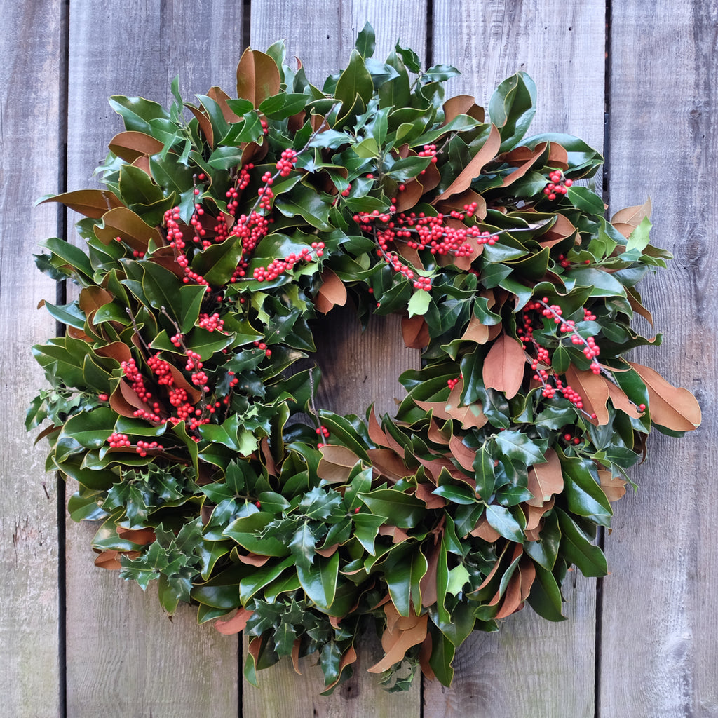 Magnolia wreath with holly greens and berries designed by Michler's Florist