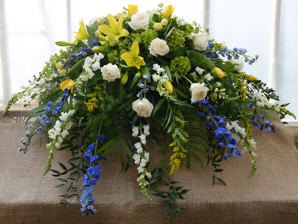 A casket spray with white roses, yellow lilies and golden rod from Michler's Florist