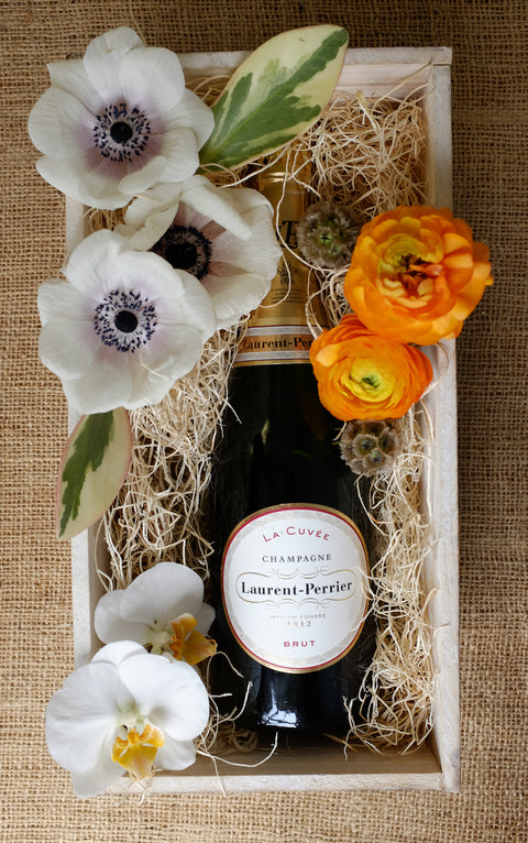 Champagne gift crate with orchid, anemone, and ranunculus blooms