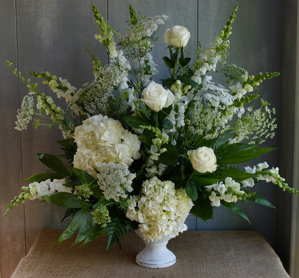 Floral arrangment with white hydrangea, white roses, white snapdragon by Michler's Floris