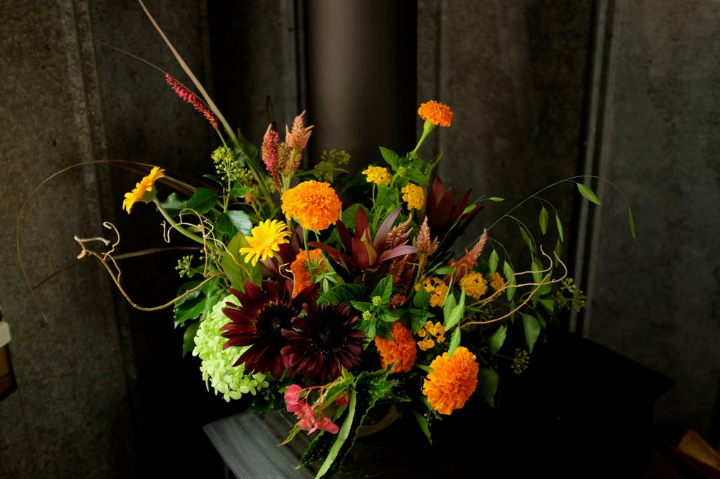 Prestige Floral Designed in an Urn in Autumn tones of Yellow, Orange and Burgundy Flowers.  Designed by Michlers in Lexington, KY