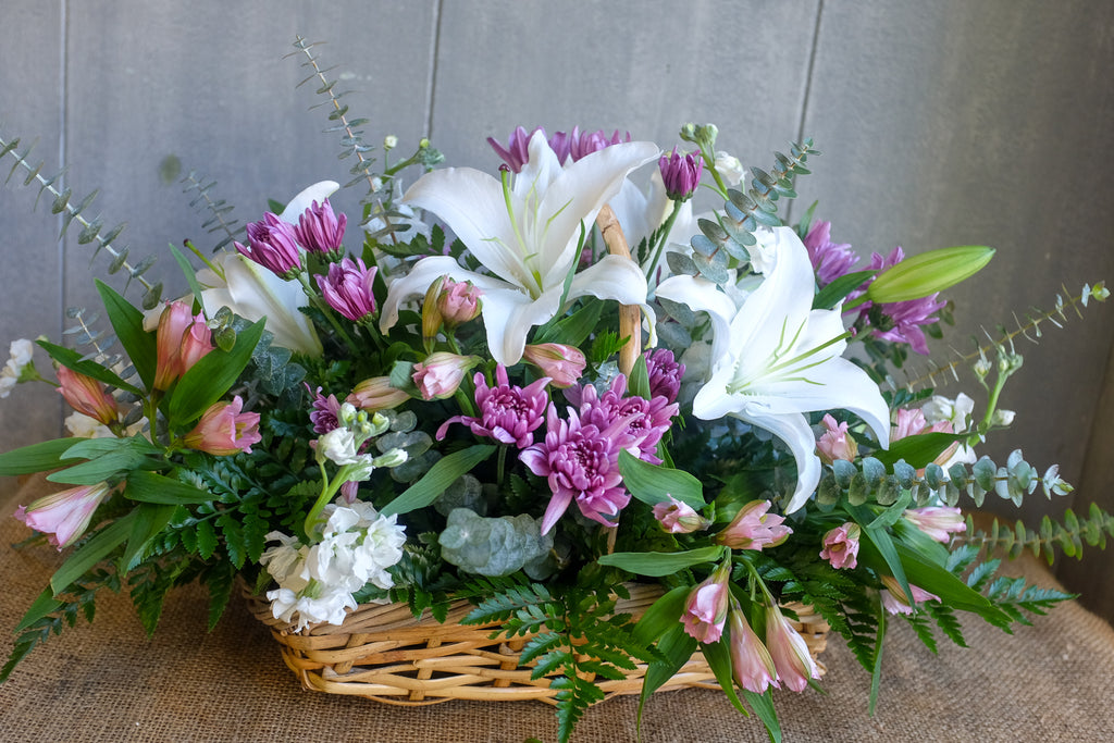 Arrangement in a basket with white lilies and purple and pink flowers