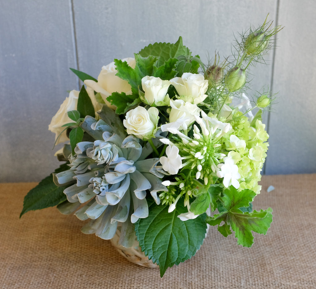 Lush floral bouquet of white and green flowers with a touch of blue