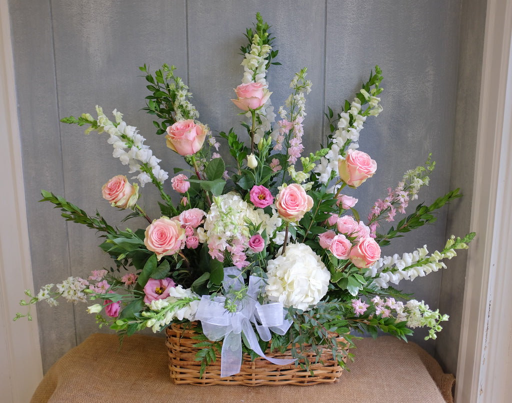 Pink and white funeral basket by Michler's Florist.