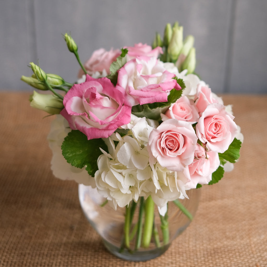 low and lush flower arrangement with roses, ranunculus, and hydrangea by Michler's