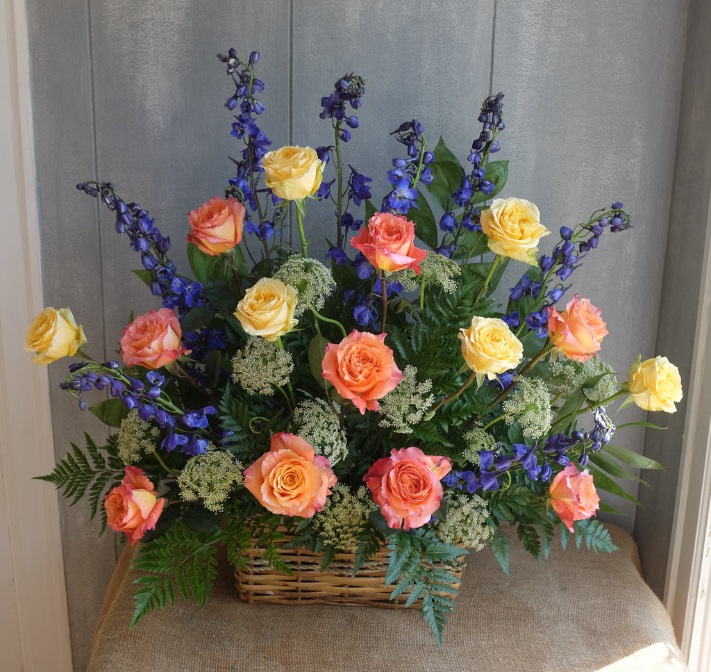 Flower basket with yellow and orange roses and blue delphinium