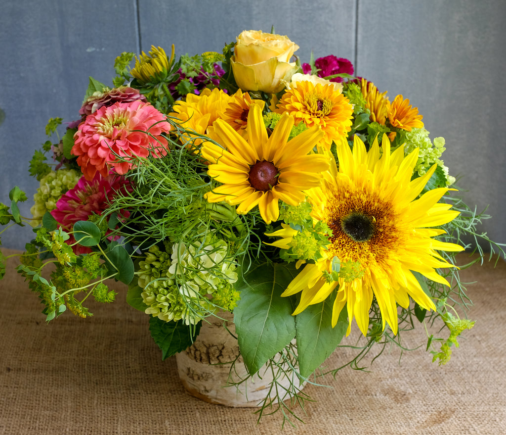 Lush bouquet filled with bright colors and summer flowers including sunflowers, zinnias, and green hydrangea designed by Michlers Florist in birch vase