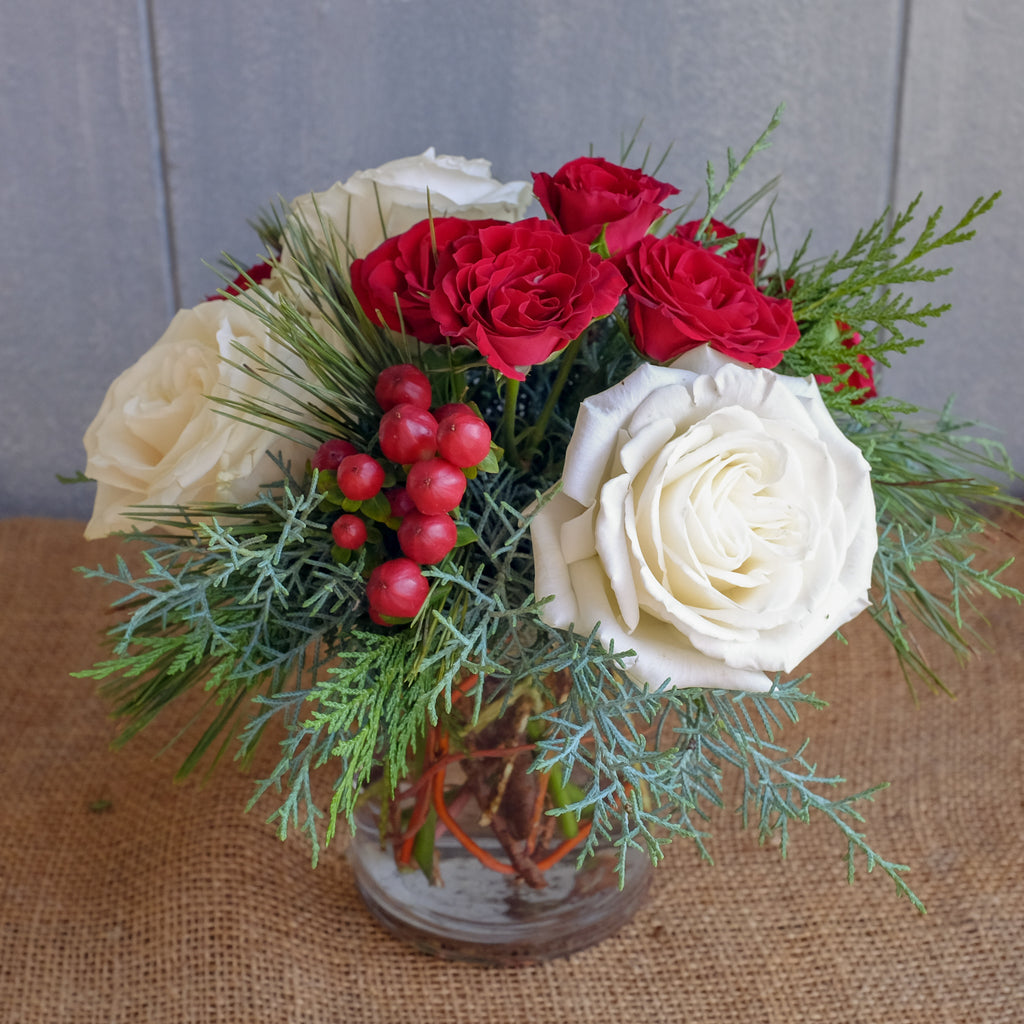 Vase of red and white flowers with christmas greens