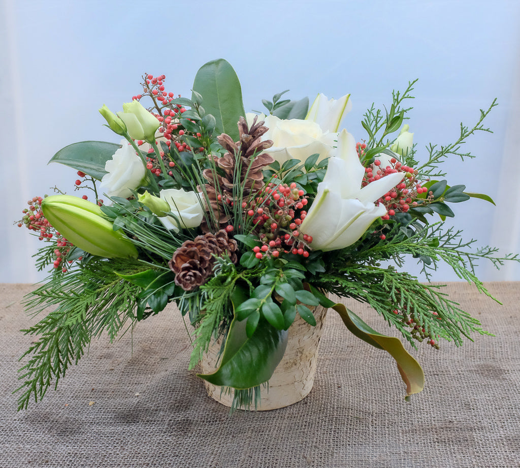 Hanover: Woodland Flower Arrangement in a birch pot with white lilies, pepperberries, pinecones, and evergreens. Designed by Michler's Florist in Lexington, KY
