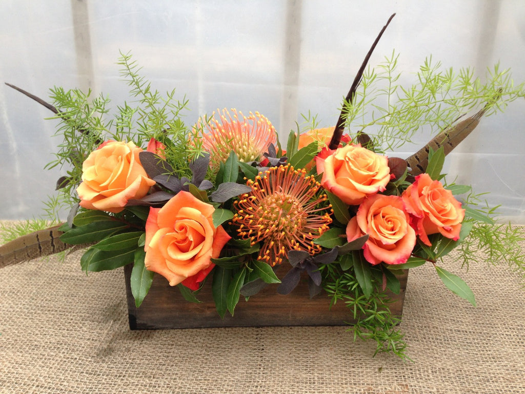 High on Rose: Thanksgiving Centerpiece with Pheasant feathers, orange Pincushion Protea, and orange Roses | Michler's Florist