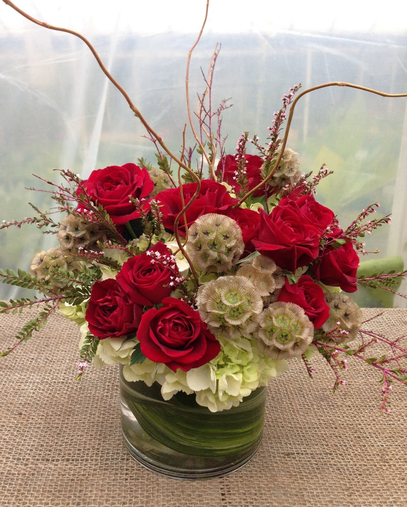 Floral Arrangement by Michler's Florist with red roses and pink heather