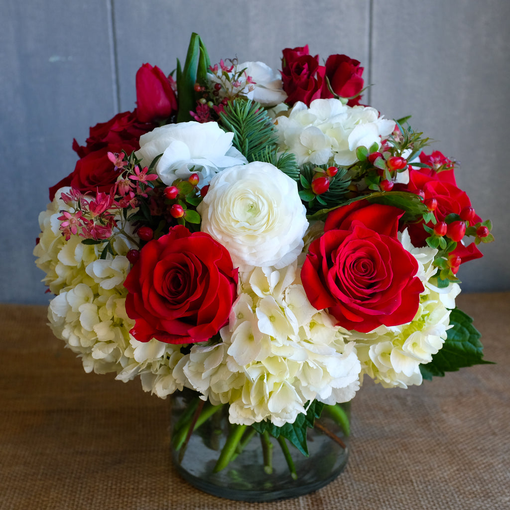 a low and lush flower arrangement with roses, hydrangea, ranunculus, and winter berries by Michler's