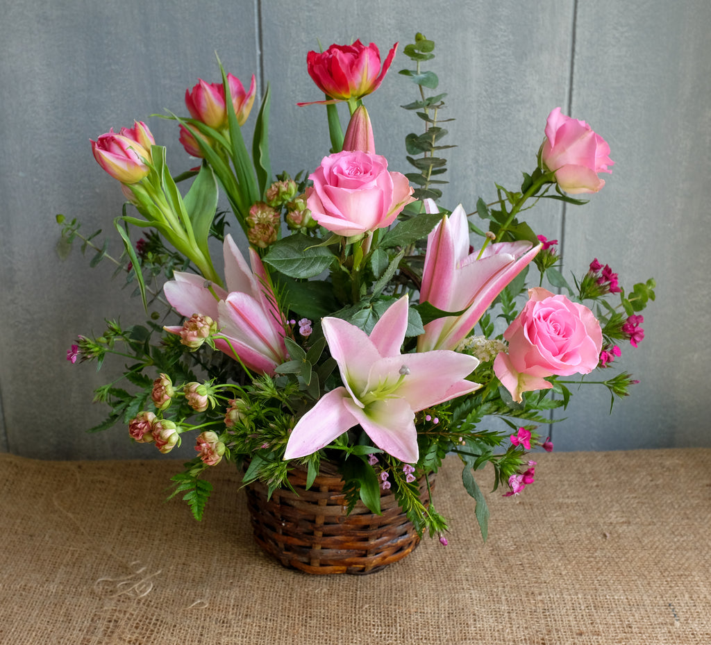 Wicker basket flower design with lilies, roses and tulips by Michler's Florist