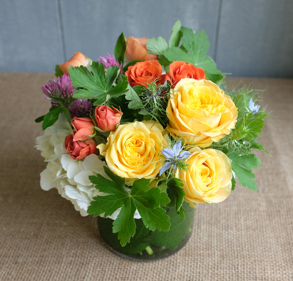 Lush bouquet of yellow and orange roses with white hydrangea and garden foliage