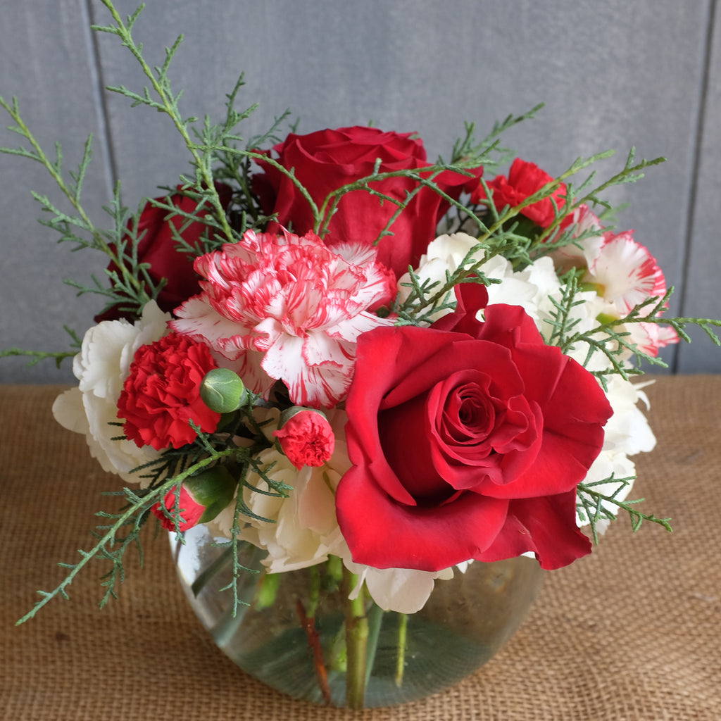 a holiday flower arrangement with roses, peppermint carnations, hydrangea, and wintergreens by Michler's