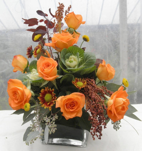 Floral arrangement with orange roses, ornamental cabbage, and eucalyptus