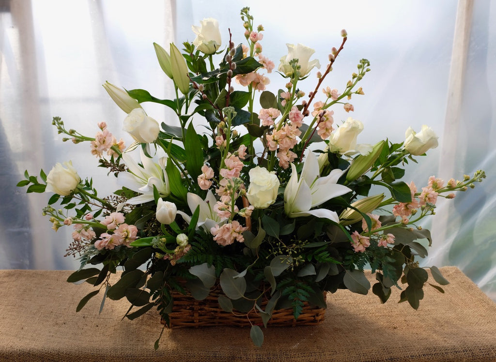 Lisbon: Wicker funeral basket with white roses, lilies and peach stock. Designed by Michler's Florist in Lexington, KY