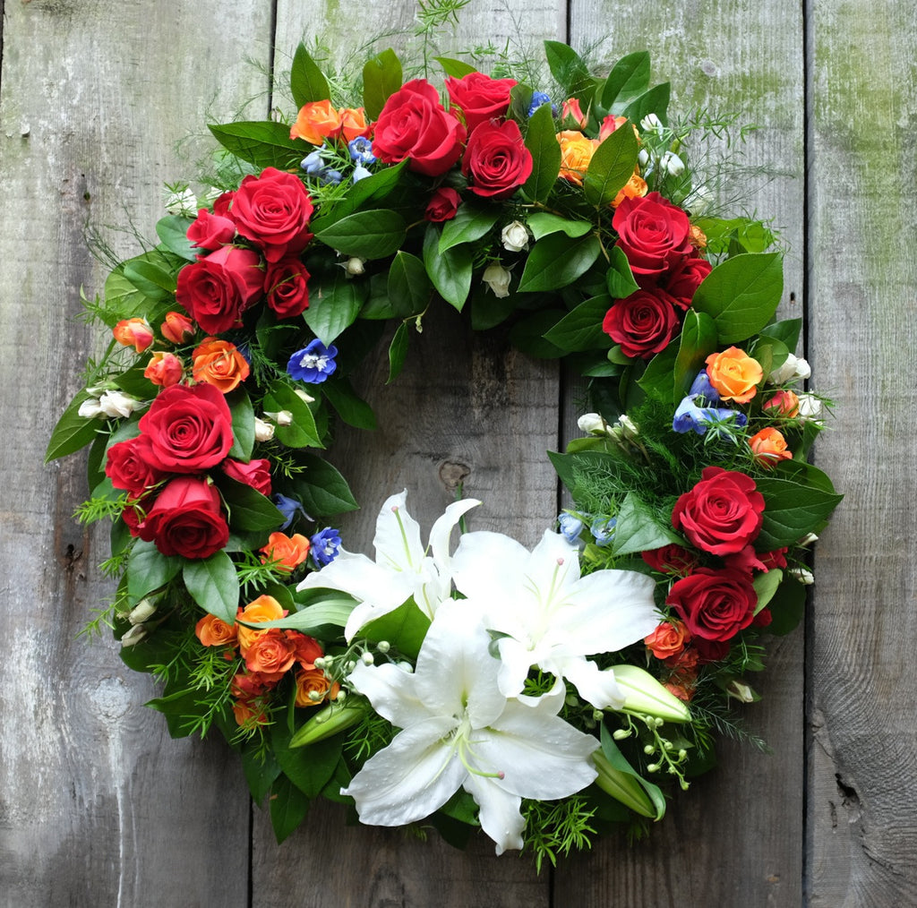Luxembourg Sympathy Funeral Wreath with Red and Orange Roses, and White Lilies. Designed by Michler's Florist in Lexington, KY