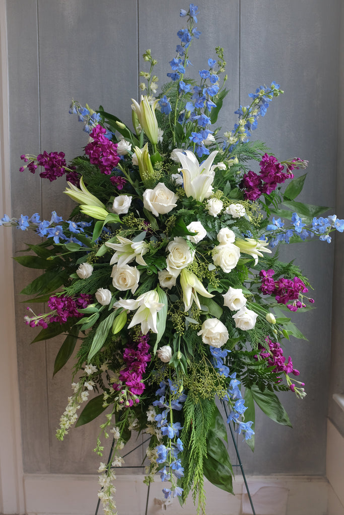 floral easel spray with lilies, roses, seeded eucalyptus, and stock by Michler's