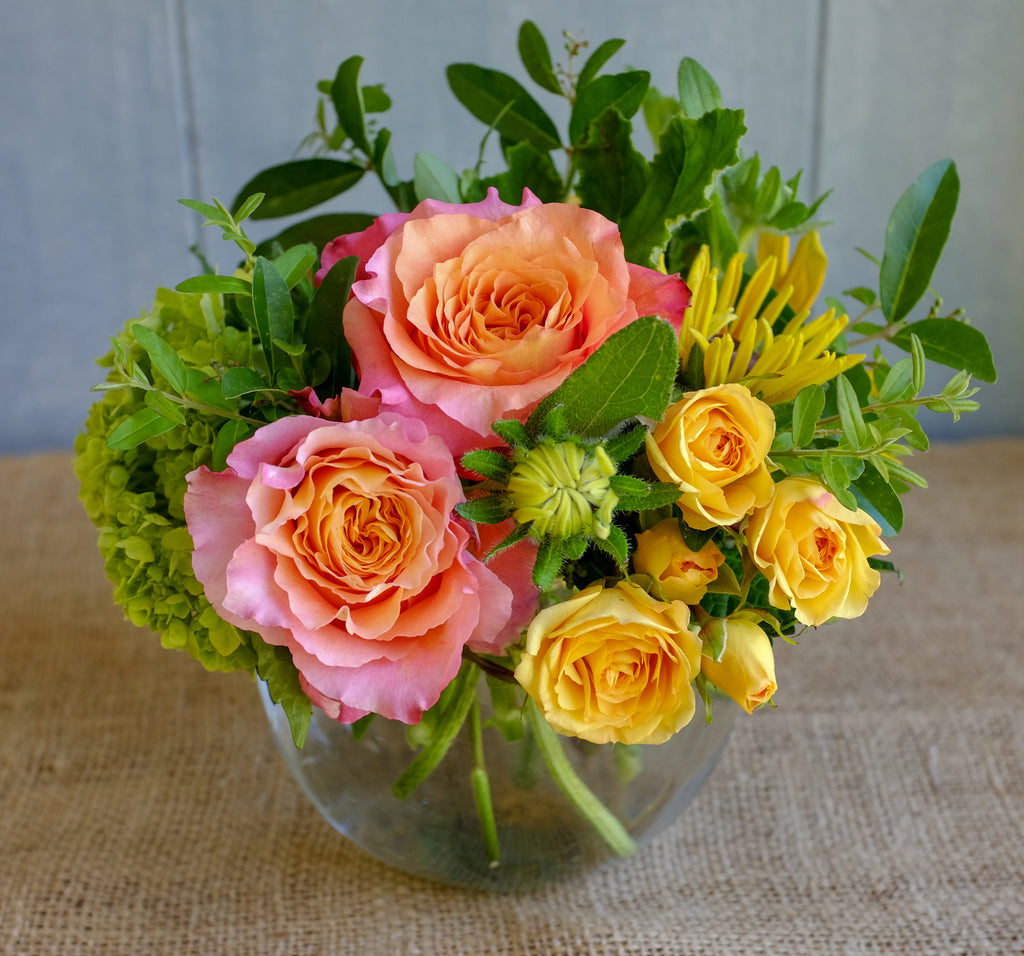 Cheerful low and lush bouquet with orange and yellow roses designed in bubble bowl