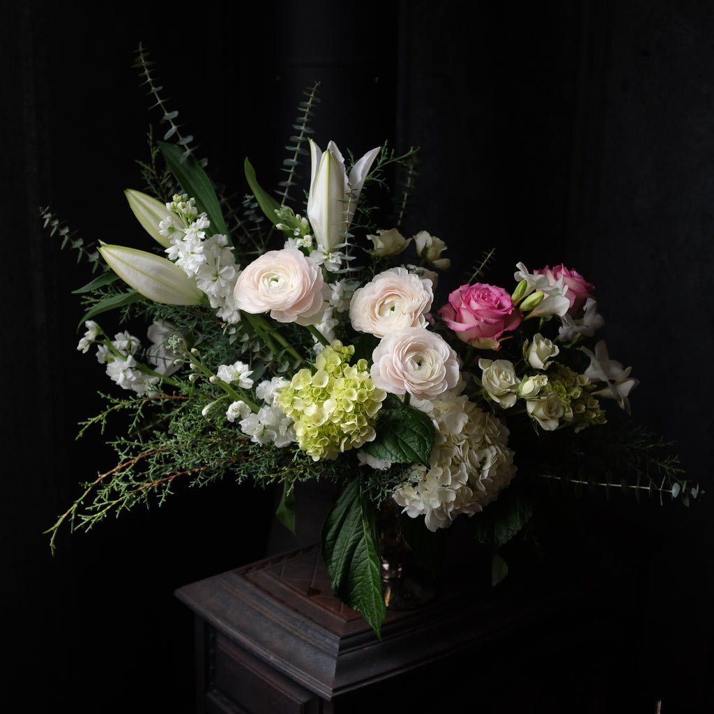elegant floral design with lilies, ranunculus, eucalyptus, and stock by Michler's