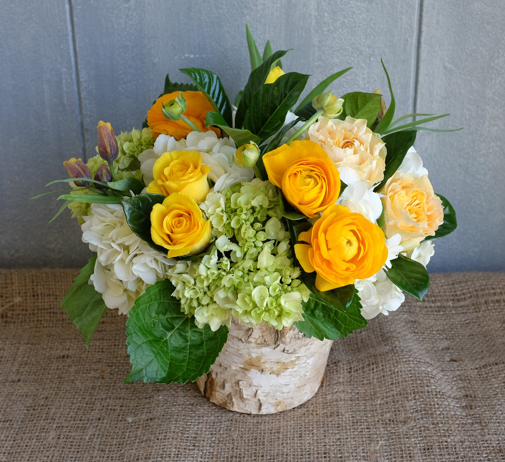 Bouquet of Yellow Ranunculus, Hydrangea, Roses and seasonal foliage.