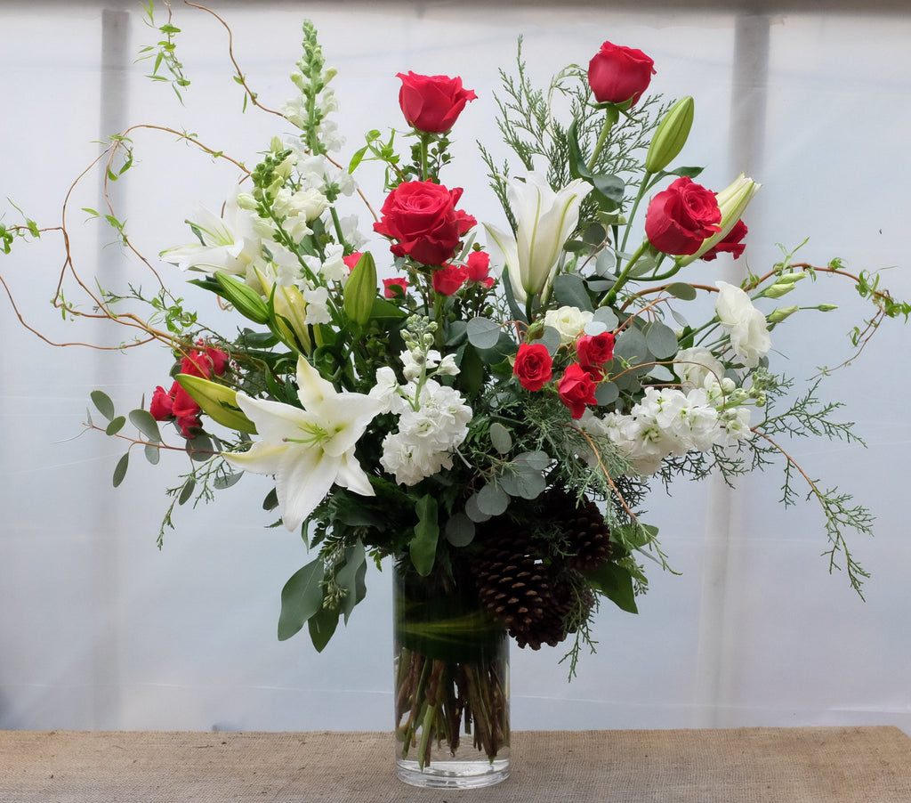 Large vase arrangement with red roses, lilies, branches, and matthiola. Designed by Michler's Florist in Lexington, KY