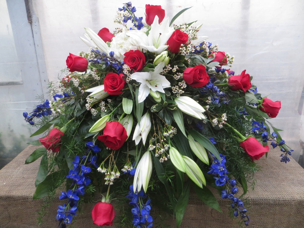 Patriotic Casket Spray with red roses, white lilies, and blue delphinium. Michler's Florist, Greenhouses & Garden Design