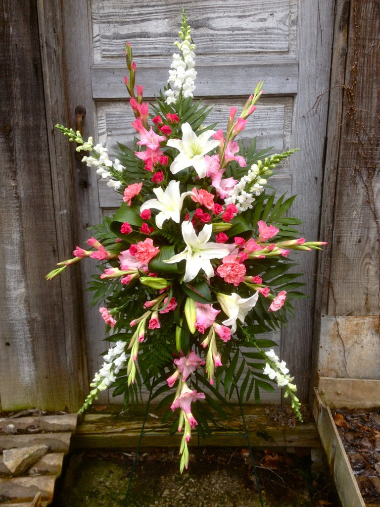 Pink and white funeral standing spray with pink Gladiolas and white Lilies. Designed by Michler's Florist in Lexington, KY