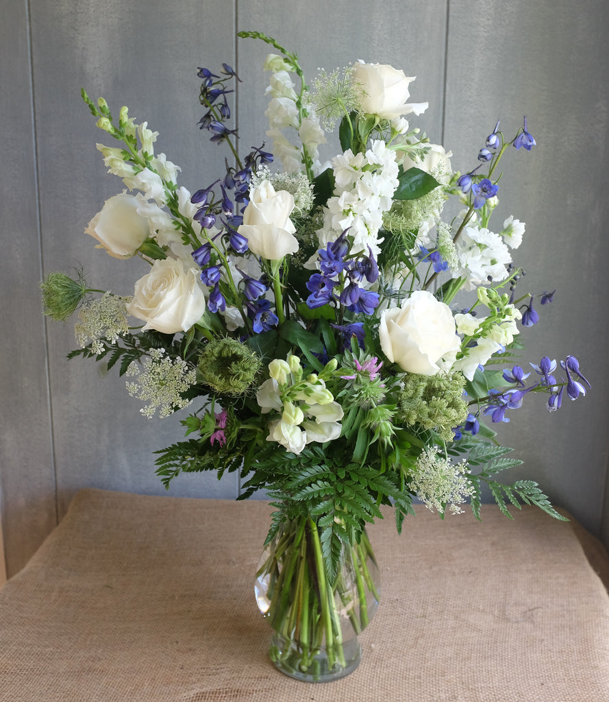 Blue and white flowers arranged in a vase.